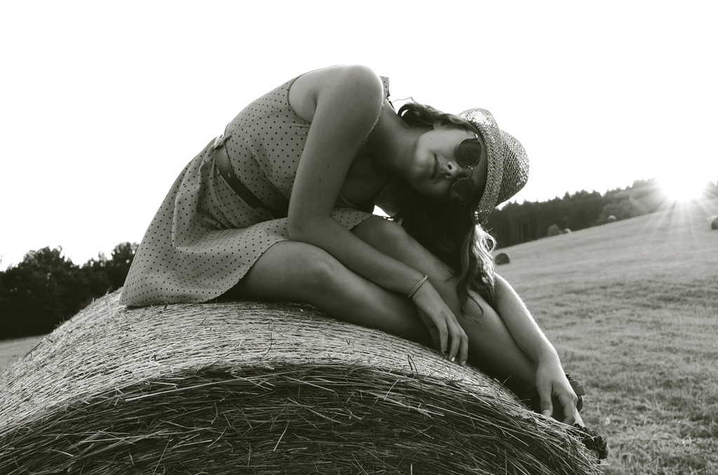 A beautiful girl on a posing in black and white on a harvested field