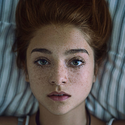Image by Beautiful portrait of a girl with freckles lying down on a pillow. The image was taken on October 22, 2014 by maximilianmair. This photo is licensed under common creatives CC2 for free personal and commercial usage. Please refer to the link below for proper license description.
